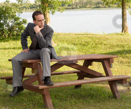 Young Businessman Thinking stock photo, A young businessman sitting on a park bench outside, thinking of work by Richard Nelson