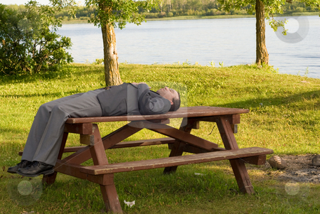 Work Break stock photo, A young businessman lying on a table outside in a park by Richard Nelson