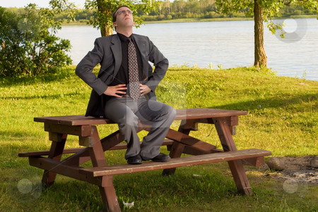 Businessman Relaxation stock photo, A young businessman wearing a grey suit doing deep breathing exercises by Richard Nelson