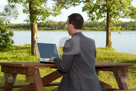 Business Work stock photo, A businessman working on a laptop outside in a park by Richard Nelson