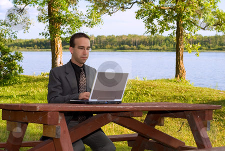 Businessman Working Outside stock photo, A young caucasian businessman working on a laptop computer outside in a park by Richard Nelson