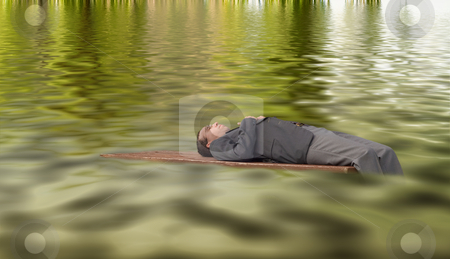 Dreaming Businessman stock photo, A young businessman stranded on some drift wood, floating on some water by Richard Nelson