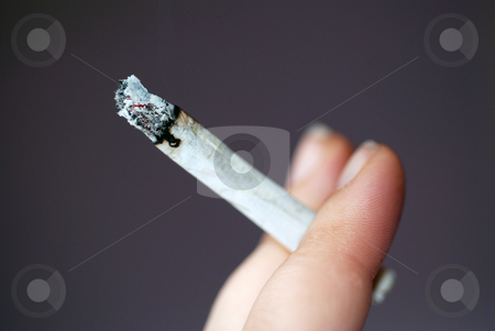 Smoking  stock photo, A photograph of a hand holding a roll-up cigarette or joint. by Philippa Willitts