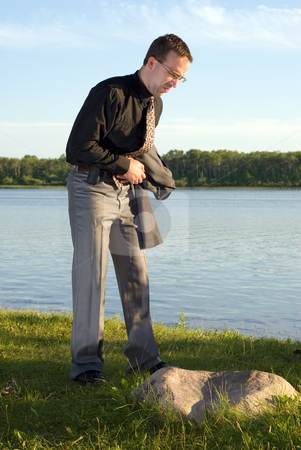 Businessman with Stomach Ache stock photo, A young businessman holding his stomach at the lake, because he has a stomach ache by Richard Nelson