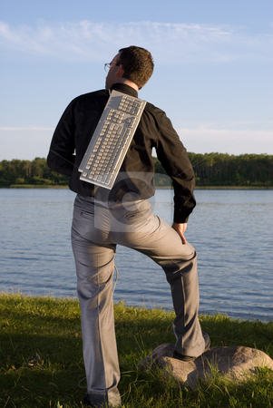 Technology stock photo, A young businessman holding a keyboard over his back by Richard Nelson