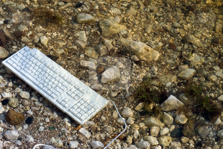 Keyboard stock photo, A keyboard that was thrown in the water on some rocks by Richard Nelson