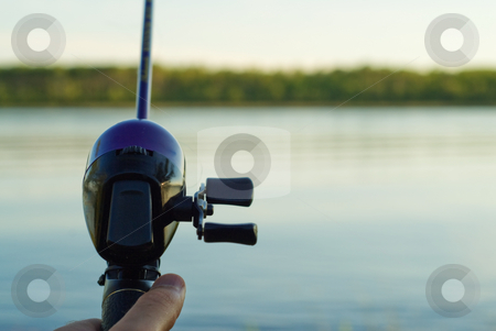 Fishing Reel and half pole stock photo, Closeup of a fishing reel casting over a lake by Richard Nelson