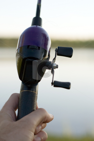 Fishing reel closeup stock photo, Close-up of a hand and a fishing pole by Richard Nelson