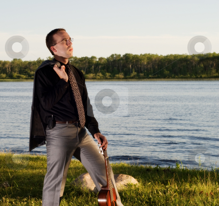 Businessman stock photo, A young businessman standing by a small lake with his guitar by Richard Nelson