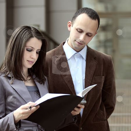 Client ready to sign the deal stock photo, Client looking at a contract outdoors next to a business man by Claudia Veja