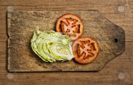 tomatoes and lettuce stock photo, Cut tomatoes and lettuce on cutting table. by Pablo Caridad