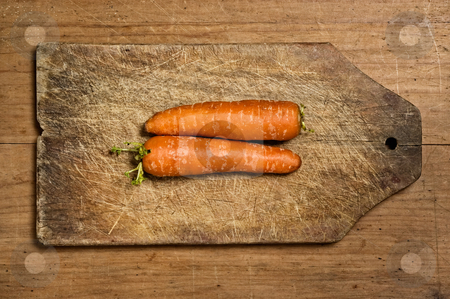 Two fresh carrots. stock photo, Two fresh carrots on wooden cutting table. by Pablo Caridad