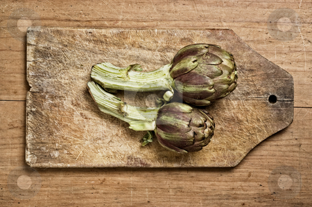 Fresh artichokes stock photo, Artichokes on a wooden cutting table, studio shot. by Pablo Caridad