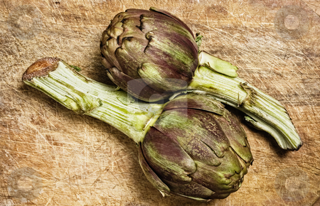 Fresh artichokes stock photo, Artichokes on a wooden cutting table, studio shot. by Pablo Caridad