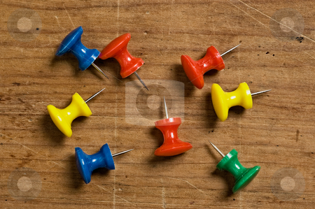 Assorted pushpins stock photo, Assorted pushpins on different colors on wooden board. by Pablo Caridad