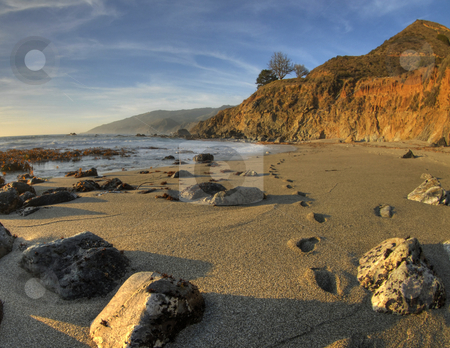 Steps in the Sand stock photo, Steps in the sand at Big Sur, California with beautiful sand, cliffs, sky and ocean in the background and rocks in the foreground. by A Cotton Photo