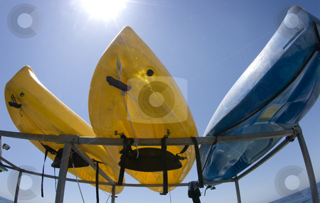 Kayaks on Boat Rack stock photo, One blue and two yellow kayaks on a rack at the beach with a bright sunny clear blue sky and the ocean in the background. by A Cotton Photo