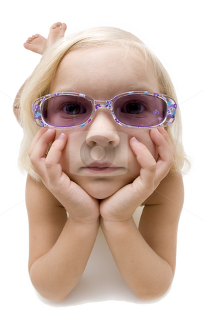 Young girl with cool sunglasses stock photo, Little girl laying on her stomach on white background wearing glasses and resting her head on her two hands. by A Cotton Photo