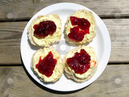 Cornish cream tea.  Strawberry jam and clotted cream scones on a park picnic bench. stock photo, Cornish cream tea.  Strawberry jam and clotted cream scones on a park picnic bench. by Stephen Rees