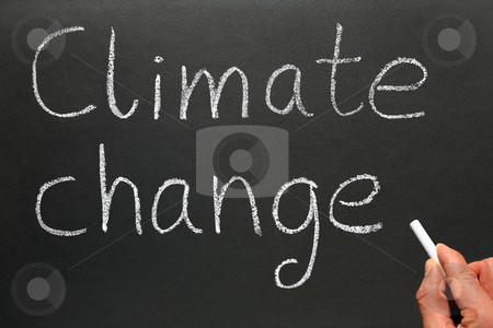 A teacher writing Climate change on a blackboard. stock photo, A teacher writing Climate change on a blackboard. by Stephen Rees