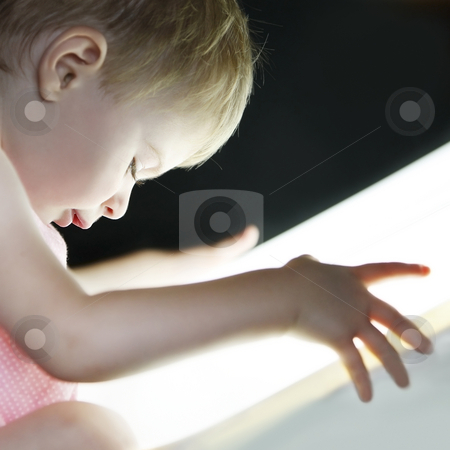 Exploring the world stock photo, Profile of a baby girl looking very interested to a bright light close to her face by Claudia Veja