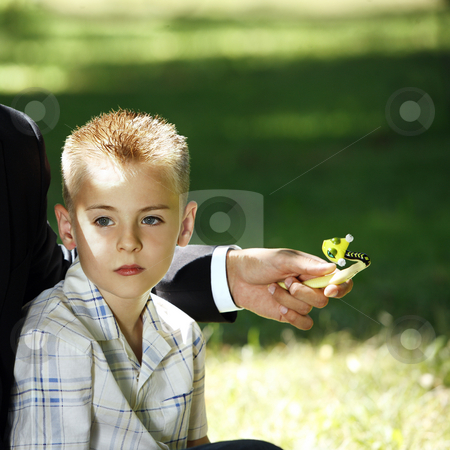 Boy sitting stock photo, Young blond boy with blue eyes relaxing in the nature next to a man with a toy in his hand by Claudia Veja