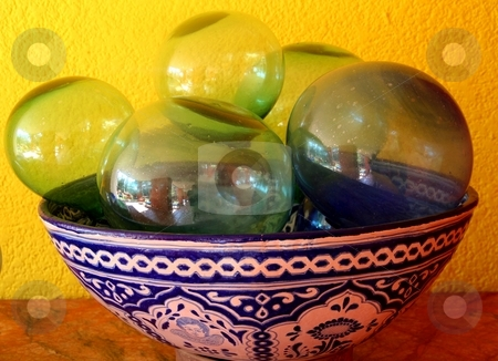 Glass ornaments in bowl stock photo, Blown glass ornamental balls of various colours in earthenware Mexican bowl by Wes Shepherd