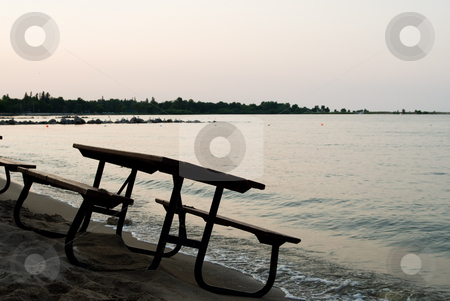 Picnic Table By The Lake stock photo, A wooden picnic table located on the beach by Richard Nelson