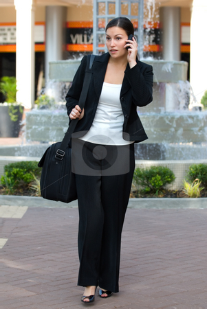 Female business person talking on cell phone stock photo, A young attractive female business professional outside talking on a cell phone and carrying a notebook computer by Vince Clements