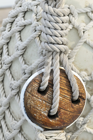 Old wooden block stock photo, Close-up of an old block on a sailboat with a bumper covered by a rope net in background by Massimiliano Leban