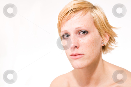 Blond girl with short hair who is feeling sad stock photo, Studio portrait of a sad looking short haired blond girl by Frenk and Danielle Kaufmann