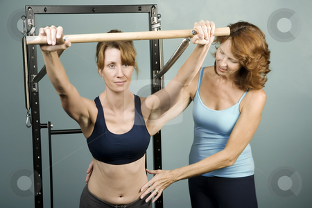 Pilates with a Trainer stock photo, Athletic woman working out with a personal trainer by Scott Griessel