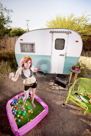 Woman flexing in a play pool stock photo, Colorful young woman flexing in a play pool by Scott Griessel