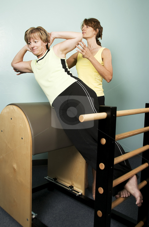Workout with a Personal Trainer stock photo, Personal Trainer Supervises a Woman Working Out on Equipment by Scott Griessel