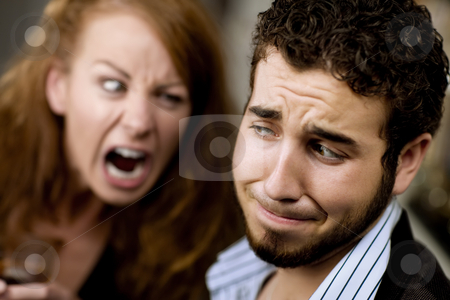 Woman Yells at Man stock photo, Young woman with cocktail yells at a man at party by Scott Griessel