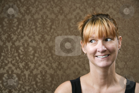 Woman Smiling stock photo, Pretty woman smiling in front of a gold-flocked wallpaper background by Scott Griessel