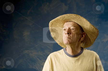 Man in a Cowboy Hat stock photo, Senior man in a straw hat in front of blue set wall by Scott Griessel