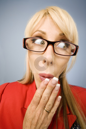 Shocked woman in red making a funny face stock photo, Woman in red with her hand in front of her face by Scott Griessel