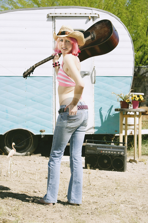 Woman in front of Travel Trailer stock photo, Pretty Woman Front of Vintage Travel Trailer with a Guitar by Scott Griessel