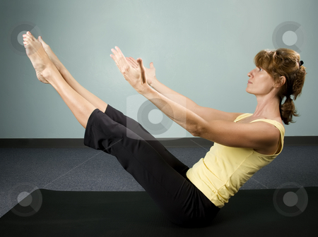 Woman Excercising stock photo, Physically fit young woman doing a balancing excercise on a mat by Scott Griessel