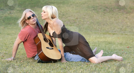 Rock and Roll Couple stock photo, Hip adult couple with a guitar outside on grass by Scott Griessel