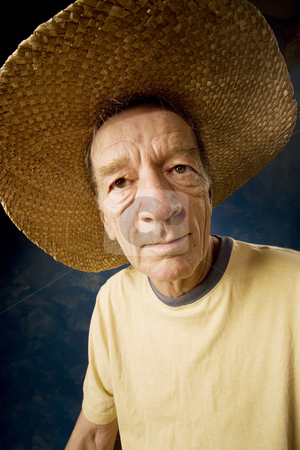 Man in a Big Straw Hat stock photo, Senior man in a  big straw hat in front of blue set wall by Scott Griessel