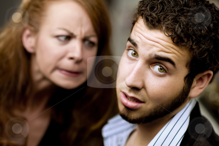 Angry Woman Looks at a Man stock photo, Young woman directs her anger at a man by Scott Griessel