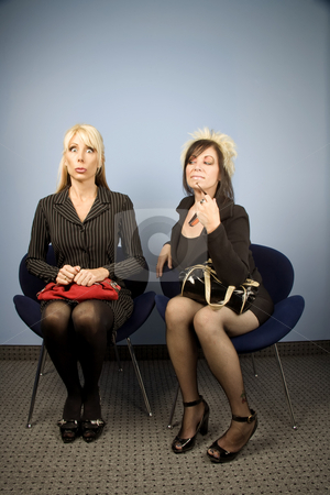 Nervous businesswoman seated next to a bold woman stock photo, Nervous businesswoman seated next to a bold woman by Scott Griessel