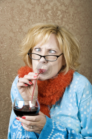 Crazy Woman Drinking Wine stock photo, Crazy woman with crossed eyes drinking wine through a straw by Scott Griessel