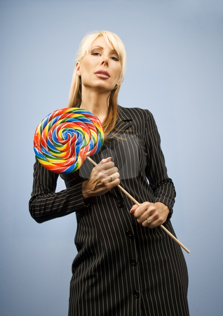 Woman with a lollipop stock photo, Woman holding a big colorful lollipop by Scott Griessel