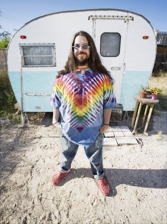 Man in Front of a Trailer stock photo, Friendly Hippie with Long Hairin Front of His Trailer by Scott Griessel