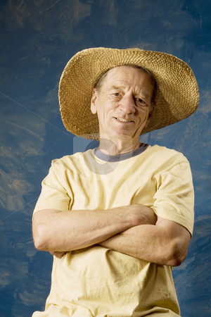 Man in a Big Straw Hat stock photo, Senior man in a straw hat in front of blue set wall by Scott Griessel