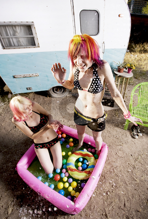 Women Splashing in a Play Pool stock photo, Colorful young women splashing in an inflatable play pool by Scott Griessel