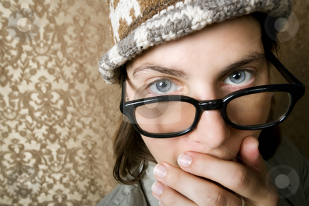 Nerdy Woman in a Knit Cap Covering Her Face stock photo, Closeup of Cute Nerdy Woman in a Knit Cap Covering Her Face With Her Hand by Scott Griessel
